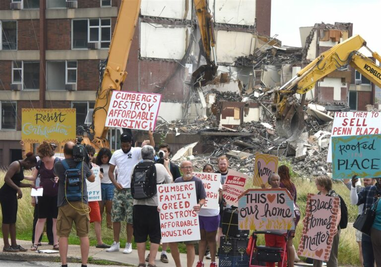 Protesters and former residents protest in front of the demolition site of the Penn Plaza in the East Liberty section of Pittsburgh