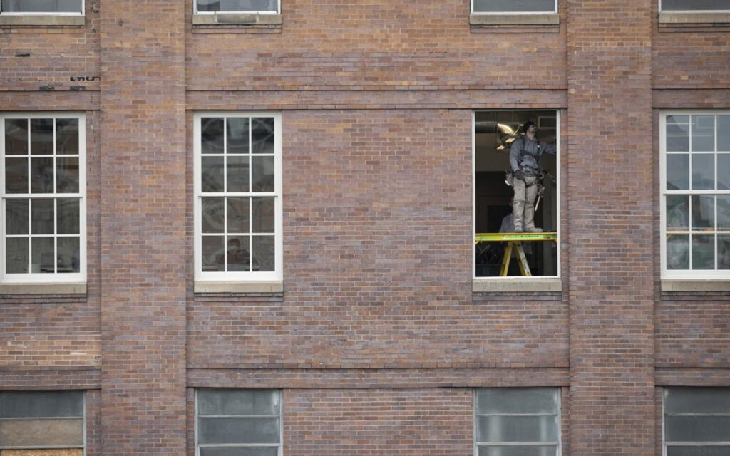 A construction worker installing a window at the Highline